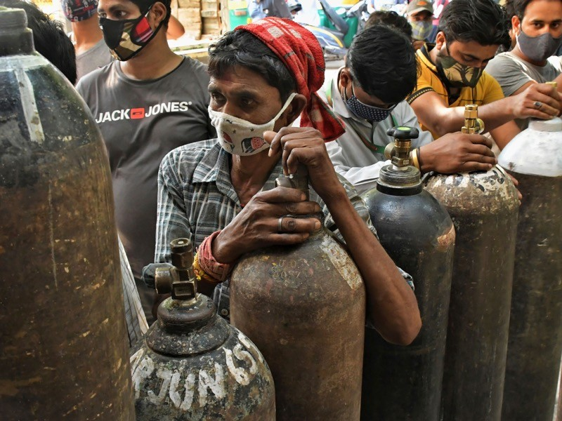 Masked people wait to refill oxygen cylinders.