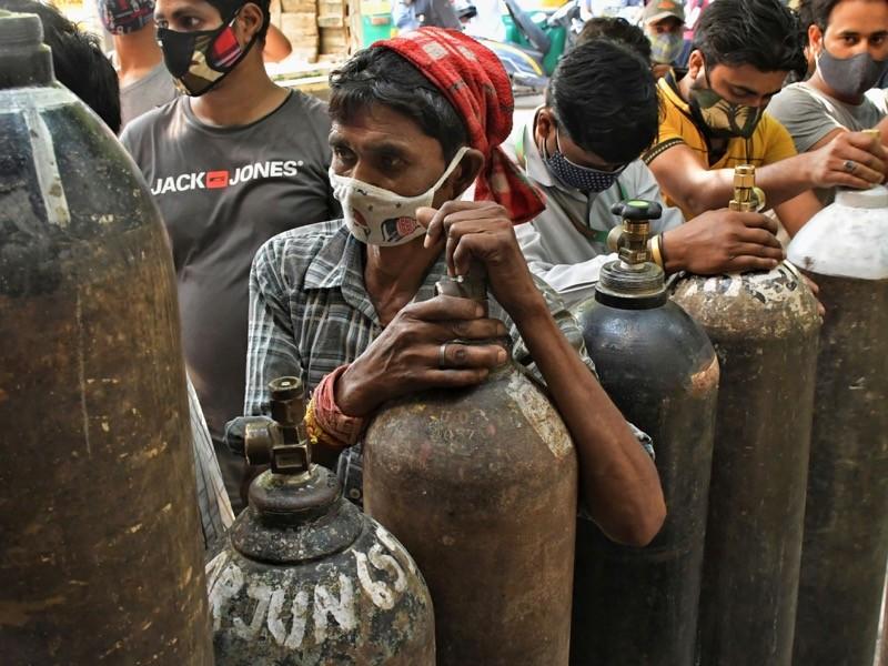 Maskeli insanlar oksijen tüplerini doldurmak için beklerler.
