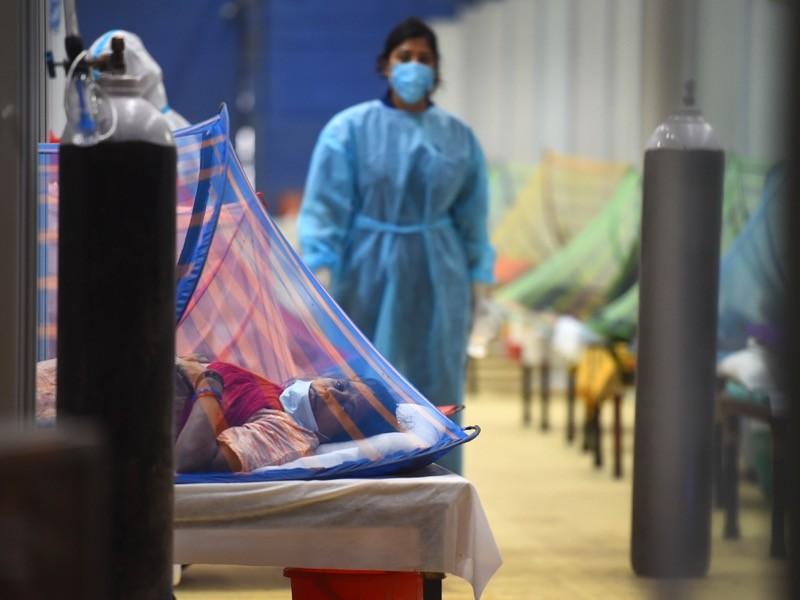 A masked health worker walks between hospital beds.