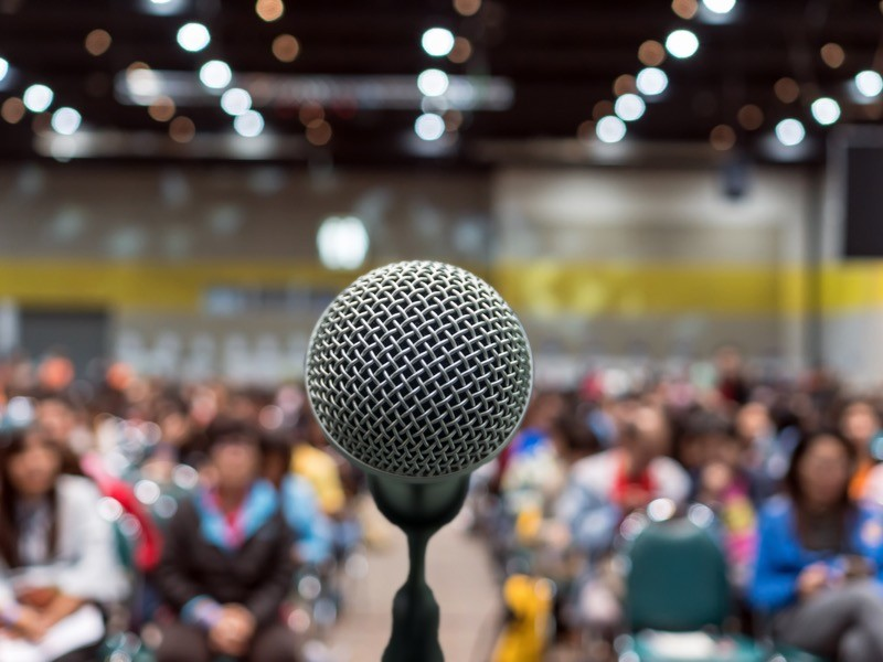 Microphone in front of a blurred audience in a conference hall.