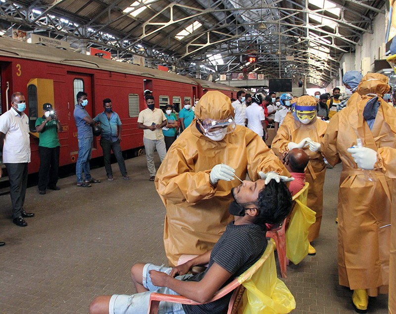 Health workers conduct COVID tests on workers at the Fort Railway Station in Sri Lanka's capital Colombo