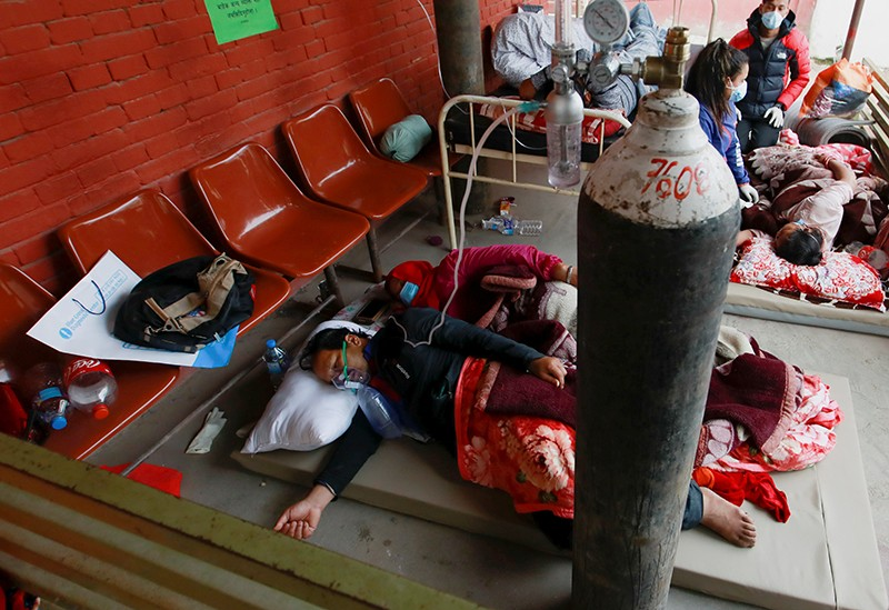 Patients receive oxygen as they sleep on the floor outside hospital due to overcrowding from COVID