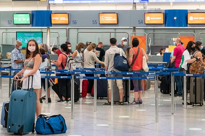Atina Uluslararası Havalimanı terminalindeki ana gidiş salonunda yüz maskesi takan yolcular