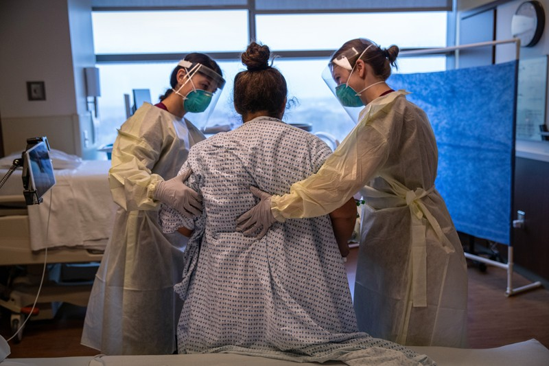 Hospital workers help a COVID-19 patient to stand up