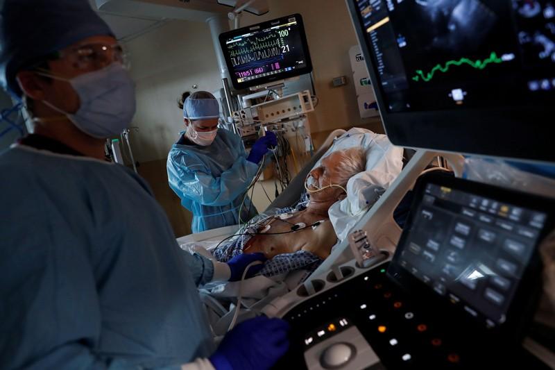 Yaşlı bir erkek hasta, ABD'deki bir yoğun bakım ünitesinde KKD'de iki medial işçi tarafından COVID-19 için tedavi ediliyor
