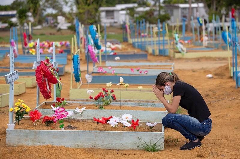 Çiçeklerle dikilmiş bir mezarda dua eden bir kadın.