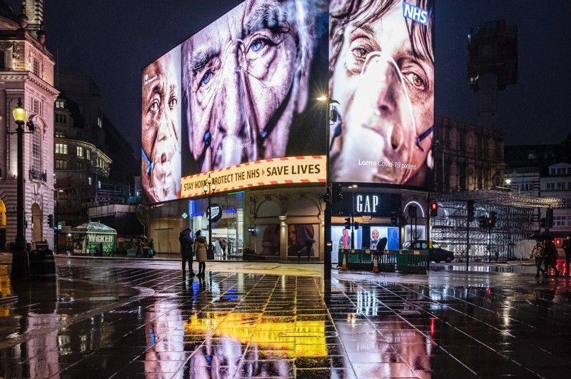 An electronic billboard at night in London shows three images of elderly people wearing oxygen masks and 'stay at home' messages