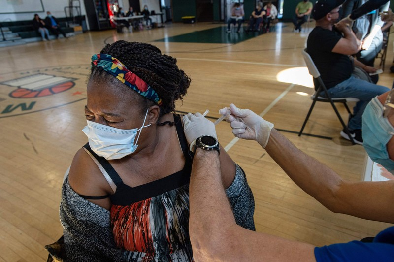 A woman in a face mask squints as she is inoculated.