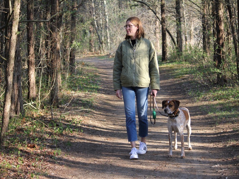 A woman walking with a dog in woodland.