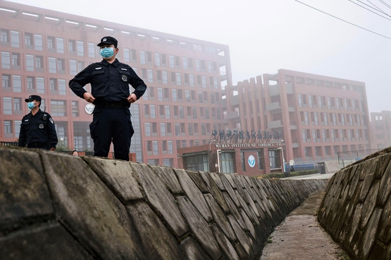 Security personnel in masks stand in front of an institutional building, in mist.