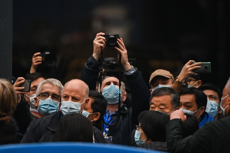 A crowd of people in masks, some taking photographs.