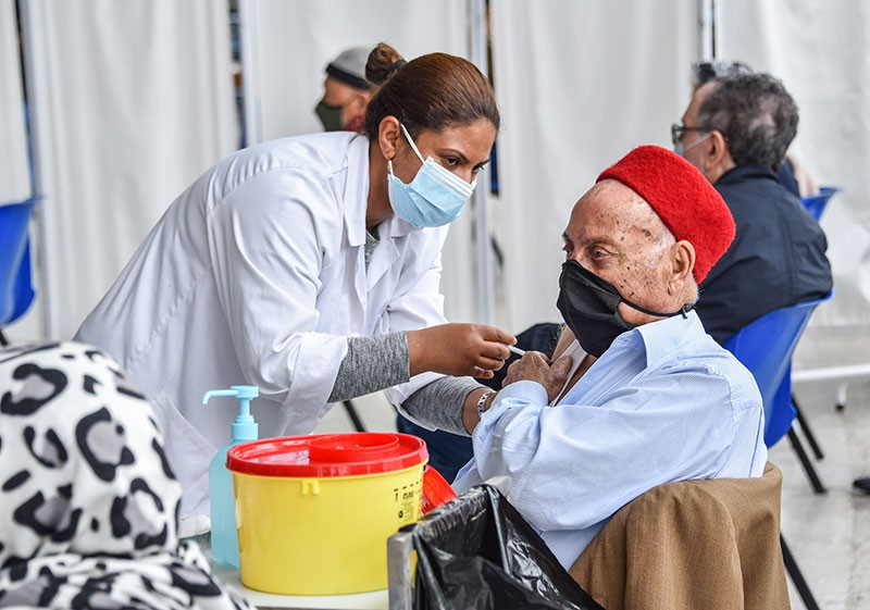 An elderly man receives a dose of the Pfizer-BioNTech COVID-19 vaccine at El-Menzah sports hall in Tunisia's capital.