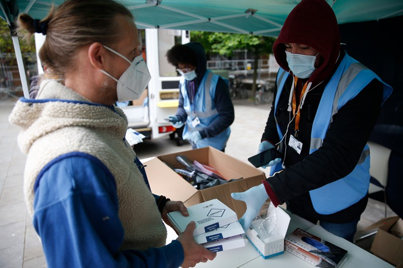 A member of the public returns PCR tests to staff member at a targeted testing site.