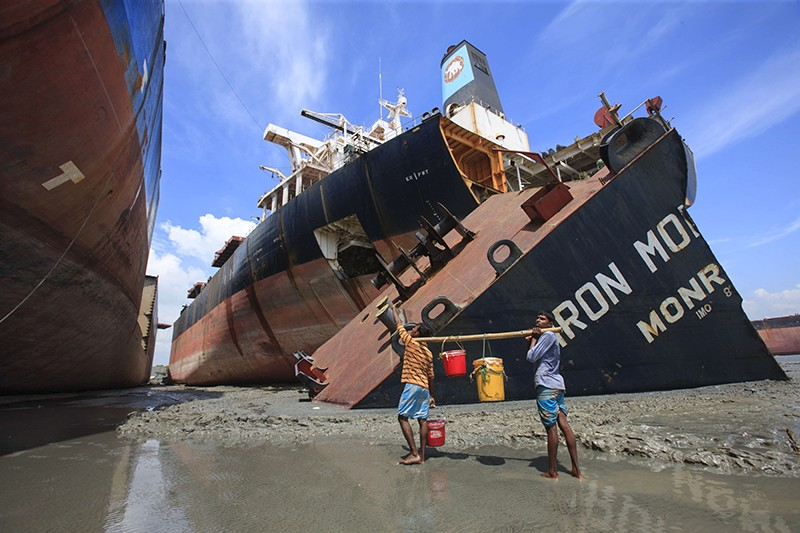 Two people carry buckets next to large ships grounded on a beach.
