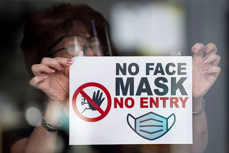 """A woman puts a sign saying """"no face mask no entry"""" in a shop window in Newport, Wales."""