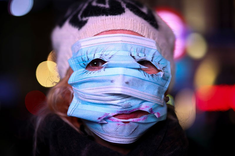 A woman uses protection masks to cover her face during the Million Mask March protest march in London.