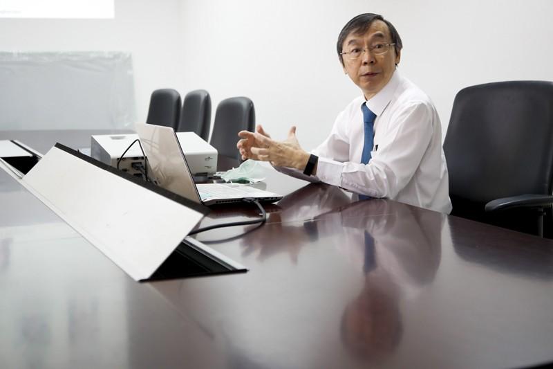 Kiat Ruxrungtham bir dizüstü bilgisayar ile toplantı masasında oturuyor, konuşuyor.