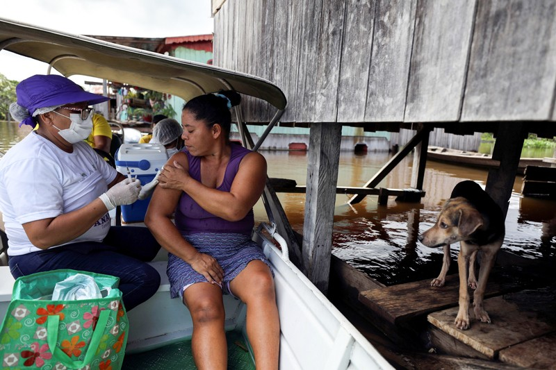 A dog looks on as a woman receives a vaccination against COVID-19 from a health worker on a boat in flood waters in the Amazon
