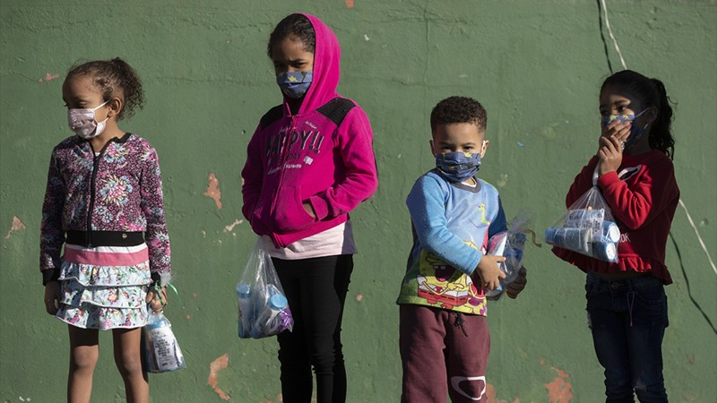 Children in Sao Paulo city hold kits including sanitizing products and face masks for kids.