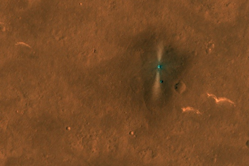 Surface of Mars with the Zhurong Mars rover surrounded by a blast pattern and its parachute and backshell lying a distance away