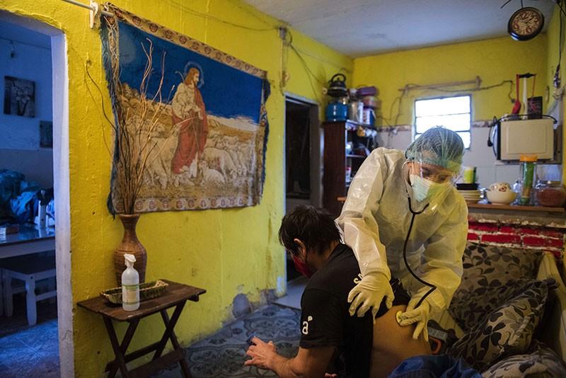 La doctora Carolina Moreira revisa al paciente de COVID-19 Carlos Broll, de 49 años, en su casa de Montevideo, Uruguay.