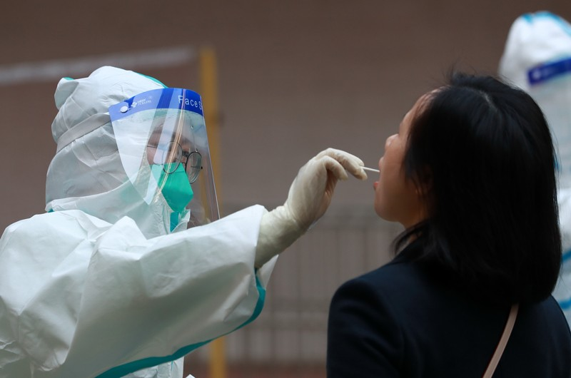 A medical worker collects a throat swab from a teacher, Wuhan