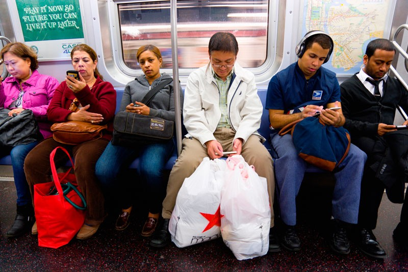 Seated passengers on the subway using their mobile phones