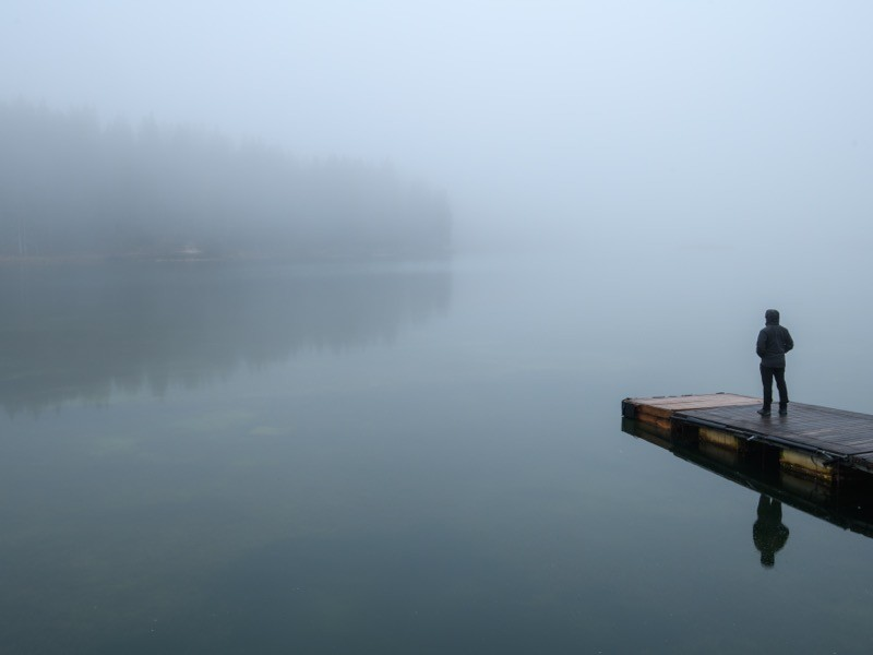 Side view of man standing on the bridge on a foggy winter day.