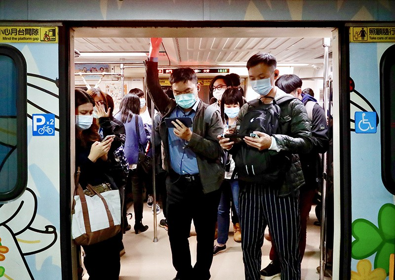 Riders wear masks and look at cell phones while on the Taipei City, Taiwan train