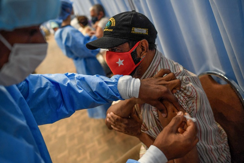 An elderly man wearing a red face covering receives a vaccine from a healthcare worker in Caracas, Venezuela