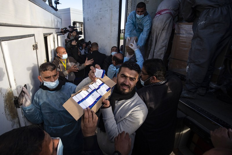 Workers unload boxes of the Sputnik V vaccine from a truck in the Gaza Strip
