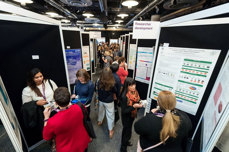 Attendees talk and observe posters during the INORMS 2018 Poster Exhibition
