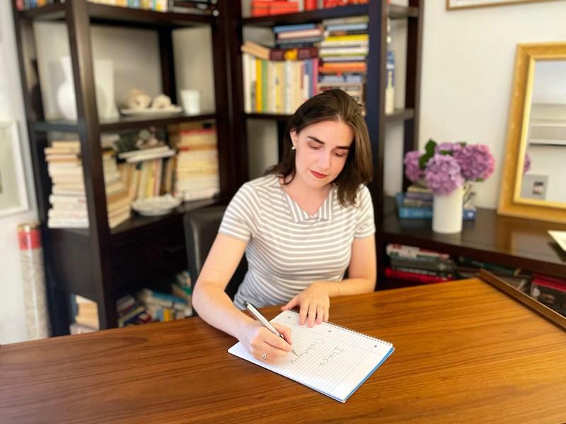 Ilinca Ciubotariu writing her name in a notebook.