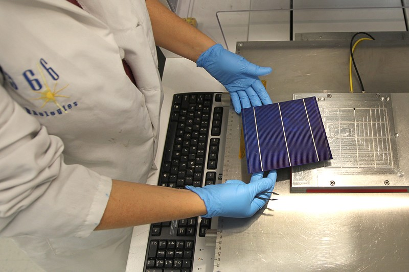 A technician handles a cell at the 1366 Technologies solar manufacturing demonstration plant