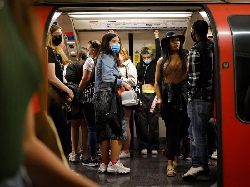 Reizigers, sommigen met gezichtsbedekking vanwege Covid-19, reizen met de Transport for London Underground (TFL).