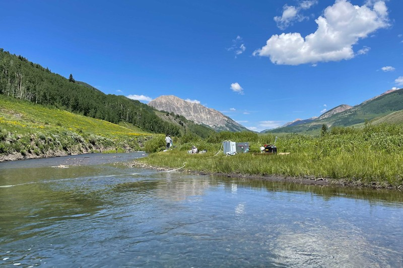 Scientists collect water samples from below the bed of the East River, Colorado with forests and mountains in the distance