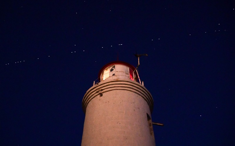 A string of the Starlink satellites streak diagonally across the sky above a lighthouse at night