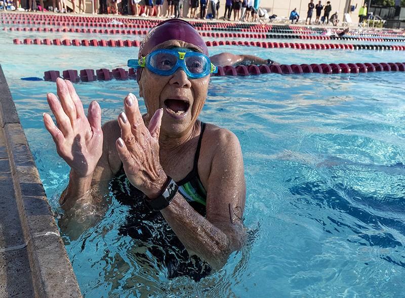 Yüzme havuzunda, bir yarıştaki zaferini kutlamak için alkışlayan yaşlı bir kadın.