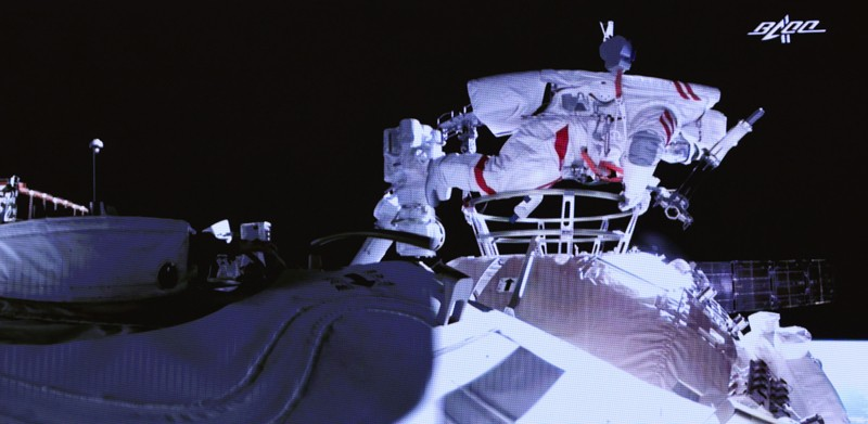 Chinese astronaut Liu Boming wearing a spacesuit exits a space station core module during a extravehicular activity