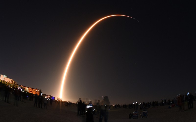 A long exposure of a SpaceX Falcon 9 rocket launch arcing through the night sky