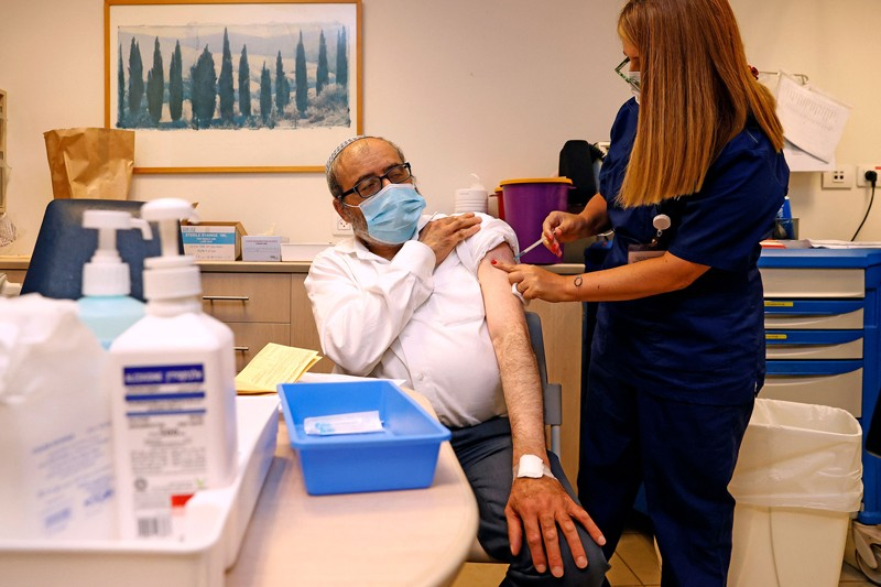 A man receives a dose of the coronavirus vaccine from a nurse in a hospital