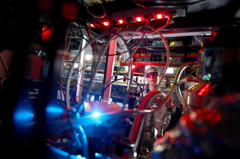 Una donna che indossa occhiali di sicurezza colorati può sembrare circondata da un groviglio di fili e apparecchiature da laboratorio laser