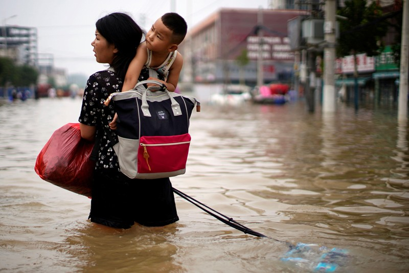 A woman carrying a child and belongings on her back wades through floodwaters in a city in China