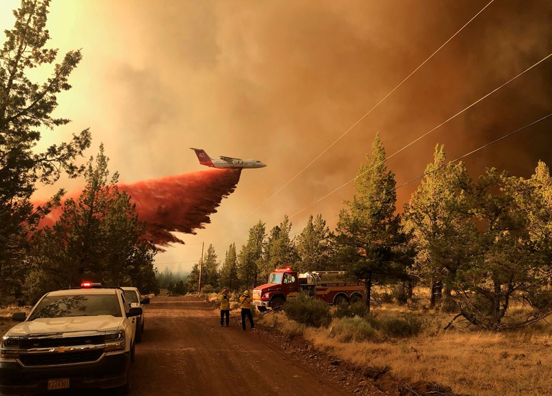 A firefighting aeroplane tanker flies over a forest fire in Oregon, dropping a cloud of red powder fire retardant