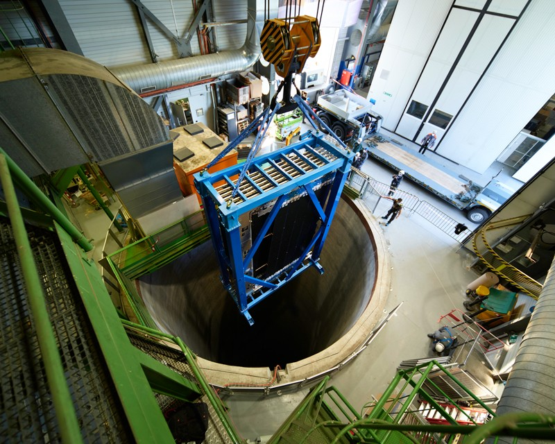 A large detector module that makes up the LHCb is lowered by a crane into a shaft in the floor of a warehouse