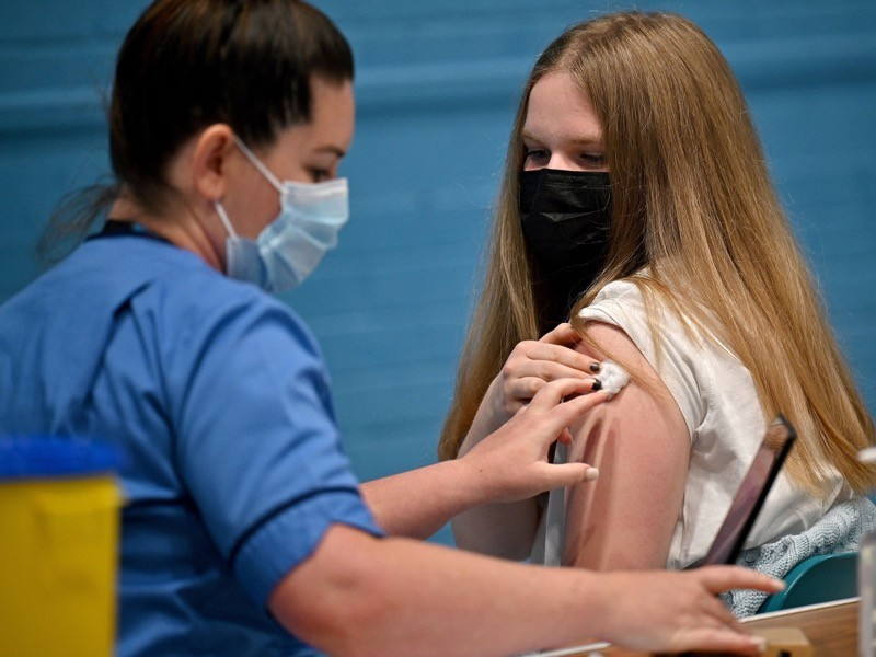 A teenager Eve Thomson receives a COVID-19 vaccine at a vaccination centre in Barrhead, UK..