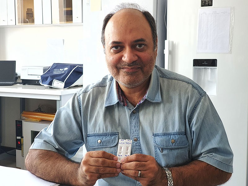 Dr.  Kayhan Azadmanesh holds a pair of tests showing the antibody response before and after vaccination.