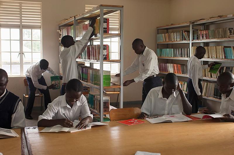 Aphunzitsi angapo ophunzira mulaibulale, akufikira mabuku kapena kuphunzira, ku College Portal Teacher Training College ku Uganda.