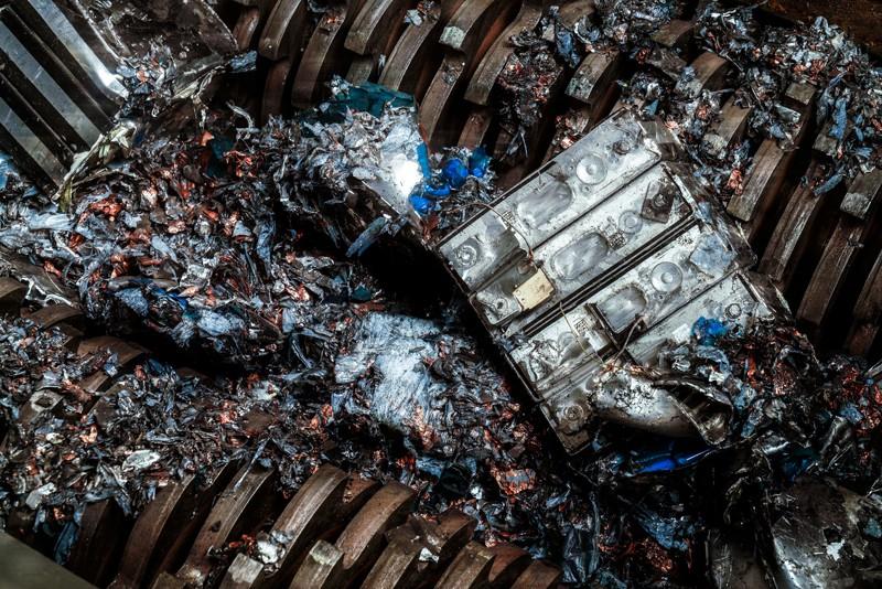 An electric car battery module entering a battery shredder with powerful metal teeth