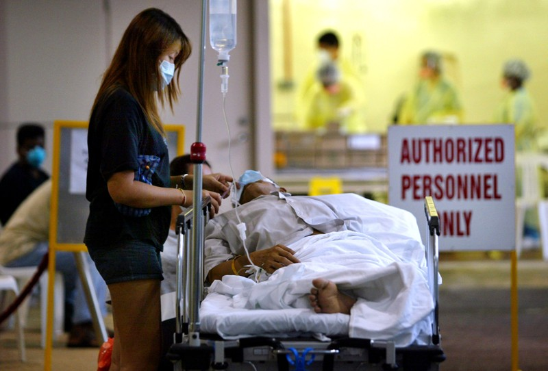A woman wearing a face mask stands over a person in a hospital bed, with an intravenous drip.